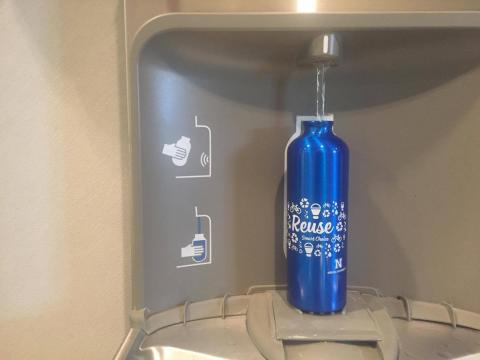 Reusable water bottle being filled at water filling station