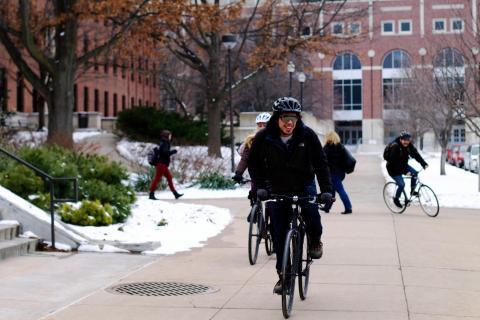 Student bikes across campus in snow